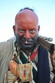 image of cree  - Angry looking warrior dressed in war paint and wearing jewelry - JPG