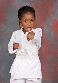 stock photo of shotokan  - Small karate girl training on colorful background - JPG