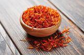 stock photo of saffron  - Saffron in wooden bowl on wooden background - JPG