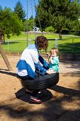 stock photo of tire swing  - A son and his mom share a tire swing at the playground of a park in Oregon. ** Note: Soft Focus at 100%, best at smaller sizes - JPG