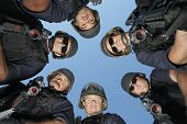 Low angle portrait of policemen standing against sky