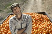 Confident middle age farmer with arms crossed standing against trailer of oranges in field