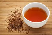 rooibos red tea  -  a white cup of a drink and loose leaves on bamboo wood background, tea made from