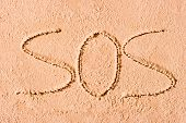 Sos Written In The Sand On The Beach In Large Letters