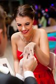 image of proposal  - young man proposing with an engagement ring to his love in a restaurant - JPG