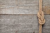 stock photo of old boat  - Ship rope knot on old wooden texture background - JPG