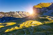 picture of shacks  - Mountains glow by morning sunlight with shacks in the national park Durmitor in Montenegro - JPG