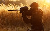 stock photo of paintball  - Paintball sport player in protective uniform and mask aiming gun before shooting at sunset - JPG