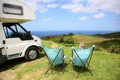stock photo of motorhome  - Senior couple relaxing in camping folding chairs - JPG