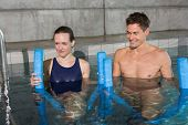 picture of day care center  - Happy couple holding foam rollers in swimming pool at the leisure centre - JPG