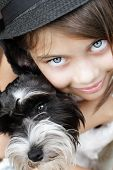 image of snuggle  - Young girl looking directly into the camera wearing a fashionable black hat and snuggling her puppy. Extreme shallow depth of field with selective focus on eyes.