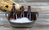 image of bucket  - Front view of three brown bottled beers crushed ice in metal bucket and baseball equipment in background on rustic wood - JPG