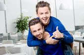 pic of piggyback ride  - Friendly brothers twins having fun riding piggyback in the white home or restaurant interior - JPG