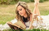 stock photo of shoe  - Portrait of romantic young woman with her shoes in the hand reading a book lying down over the grass - JPG