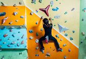 foto of climbing wall  - Girl climbing up on practice wall indoor rear view - JPG