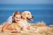stock photo of labradors  - Portrait of a cute blonde in the t-shirt and shorts with her light brown dog Labrador posing on a deserted beach on the background of the blue sea.
