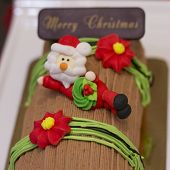 picture of yule  - Traditional Christmas Yule Log cake decorated with santa bear and fiower mazipan.