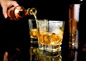picture of whiskey  - barman pouring whiskey in front of whiskey glass and bottles on black table with reflection - JPG