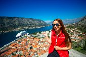 foto of vest  - Young woman traveler in red vest with backpack on the Lovcen mountain near the old city Kotor - JPG