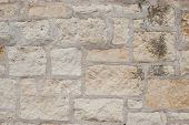 stock photo of grout  - Beige and cream stones in an outdoor wall with thick grout - JPG