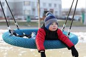 stock photo of tire swing  - Child lying on a swing at outdoor playground in spring - JPG