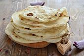 picture of pita  - Freshly baked pita bread on a wooden table - JPG