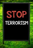 image of stop fighting  - STOP TERRORISM message on sidewalk blackboard sign against green grass background - JPG