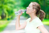 picture of cold drink  - Young beautiful woman drinking cold mineral water from a bottle  after sport fitness exercise at green summer park - JPG
