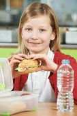 picture of school lunch  - Girl Sitting At Table In School Cafeteria Eating Healthy Packed Lunch - JPG