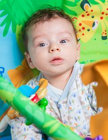 stock photo of playmate  - 3 months old baby boy playing and learning on the playmat - JPG