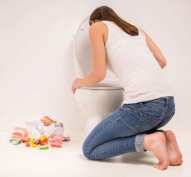 image of vomiting  - Young woman vomiting into the toilet bowl in the early stages of pregnancy or after a night of partying and drinking - JPG