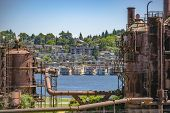 Abandoned Machines And Storage Units In A Gas Industry At Gas Works Park Seattle With Water And Home poster