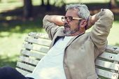 Pensive Mature Man Sitting On Bench In An Urban Park. poster