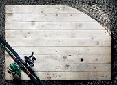 Fishing nets and fishing rod still-life on the wooden background.   poster