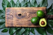 Food Background With Fresh Avocado, Avocado Tree Leaves And Wooden Cutting Board. Harvest Concept, G poster
