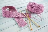 High angle view of pink woolen Breast Cancer Awareness ribbon with crochet needles on white wooden t poster