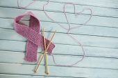 High angle view of pink woolen Breast Cancer Awareness ribbon by crochet needles with heart shape on poster