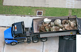 image of dump_truck  - A large dump truck filled with massive boulders - JPG