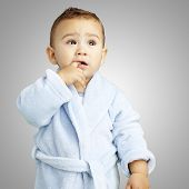picture of housecoat  - portrait of adorable infant with his finger in his mouth wearing a bathrobe over a grey background - JPG