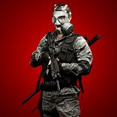 portrait of young soldier with gas mask and rifle against a red background