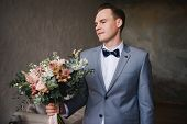 The Groom Is Waiting For The Bride In A Gray Suit. Groom Holding Bouquet And Waiting For Bride. Wedd poster