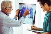 Doctors Working With X Ray Film Of Patient Chest. poster