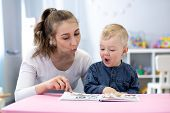 Speech Therapist Teaching Letter Pronunciation To Child Boy In Classroom poster