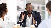 African American Businessman Coach Negotiator Speaking At Diverse Team Meeting poster