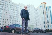 Man Standing In Yard Of City Portrait Of Young Man In Casual Clothes Standing Beside Cars In Yard Of poster