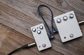 Two Vintage Guitar Pedal Effects On Wood Background poster