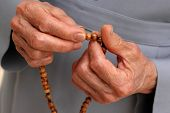 picture of prayer beads  - hand of a catholic nun counting the rosary - JPG