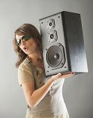 Young beautiful surprised woman with sunglasses holding big wooden speaker and listening music