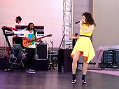 Beautiful girl in yellow dress singing