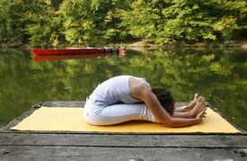 stock photo of yoga mat  - Woman doing yoga on lake in park in autumn - JPG